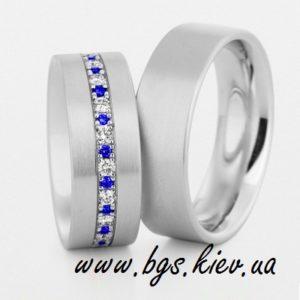 Обручальные кольца с сапфирами, кольца «Яркий акцент» в белом золоте. В женском обручальном кольце синий и белый сапфир. Мужское кольцо без камней