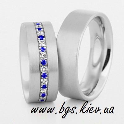 Обручальные кольца с сапфирами «Яркий акцент» в белом золоте. В женском обручальном кольце синий и белый сапфир. Мужское кольцо без камней